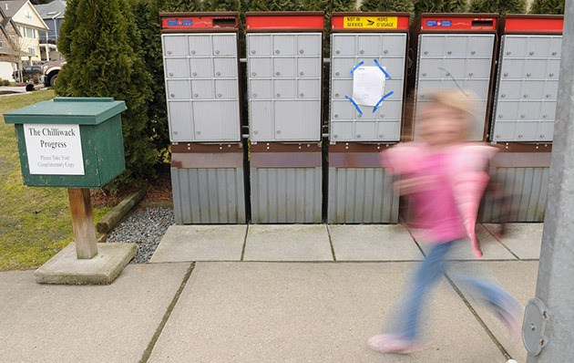 A girl runs past a community mailbox at the corner of Brookwood Place and Palmer Place that was a target of recent mail theft. The mailbox has a bright yellow sign on it reading 'Not in service'