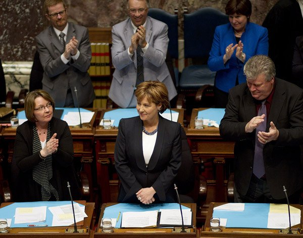 Premier Christy Clark is applauded by fellow MLAs as she takes her seat in the legislature Monday.