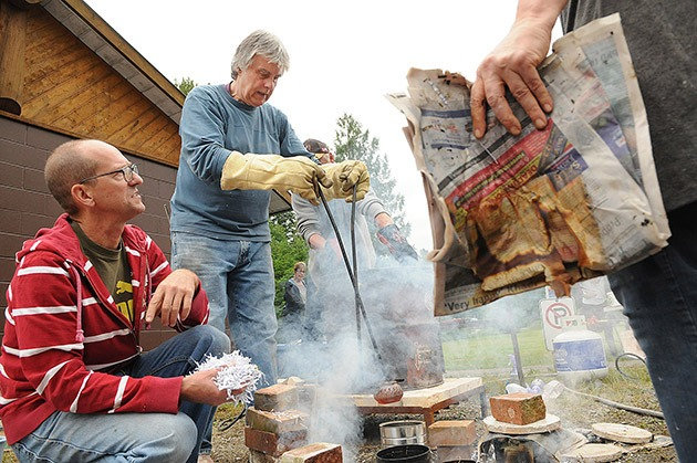 Vijaya Morrison (with gloves) of Rainforest Pottery transfers a fiery hot ceramic pot into a reduction container filled with wood chips and paper shreds during Raku in the Valley at Thompson Park in the Chilliwack River Valley on Saturday. The reduction stage extracts oxygen from the pot to create different effects on its glazed finish. More than 60 people took part in the workshop where they glazed and fired pre-made pots.