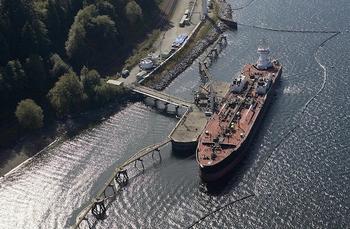 An oil tanker is boomed off and docked at Kinder Morgan's Burnaby terminal to take on oil from the Trans Mountain pipeline. The number of tankers plying Burrard Inlet would increase from five per month to 34 if the pipeline is twinned.