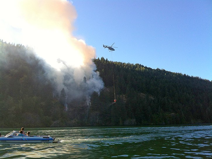 Above: People watch as a helicopter prepares to drop water on a wildfire in Cultus Lake Monday evening. Below: Charred trees and shrubs are seen in this photo taken Tuesday morning.