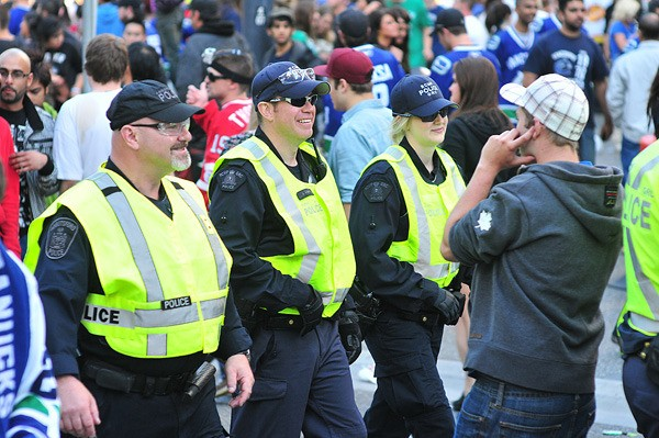 Members of the RCMP and the Abbotsford police (left) patrol Granville Street early Wednesday evening before the post-Stanley Cup riots in downtown Vancouver.