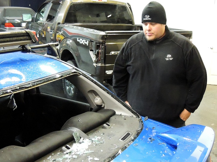Karl Nylund of Abbotsford surveys the damage to his Subaru on Wednesday afternoon. Nylund's rear window was shattered by falling ice on the Port Mann Bridge.