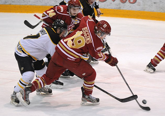 Tipper Higgins of the Chilliwack Chiefs battles Brendan Lamont of the Coquitlam Express for the puck during the first period of Saturday night's game at Prospera Centre.