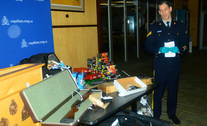 Coquitlam RCMP Cpl. Michael McLaughlin displays the items seized in a series of armed robberies across the Lower Mainland.