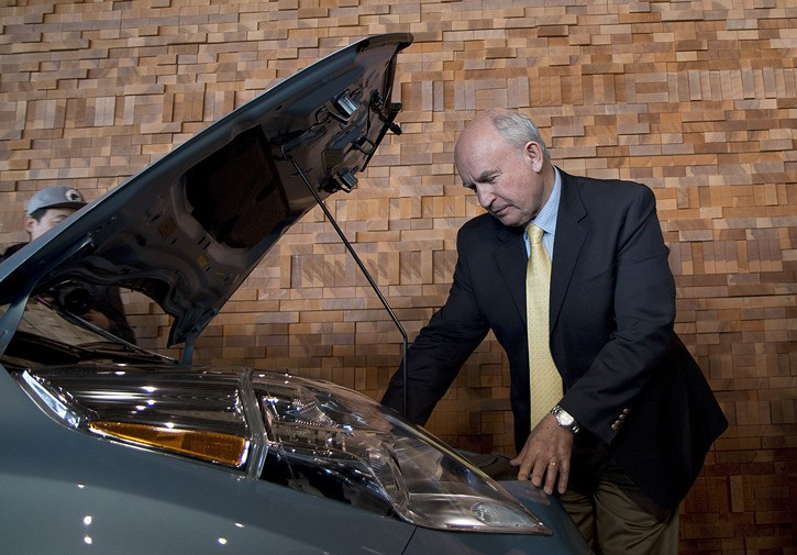 Energy Minister Bill Bennett looks at the power system of a plug-in electric vehicle on display at the Vancouver International Auto Show.