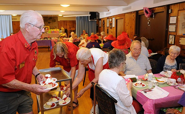 Hank Menkveld serves strawberry shortcake to guests along with fellow Lions Helena Tetteroo and Alice Cain during the Mt. Cheam Lions' first ever Strawberry Social at their hall last Saturday.