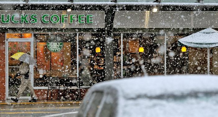 A man walks along First Avenue at Salish Plaza under an unusual April snowfall early Thursday morning.