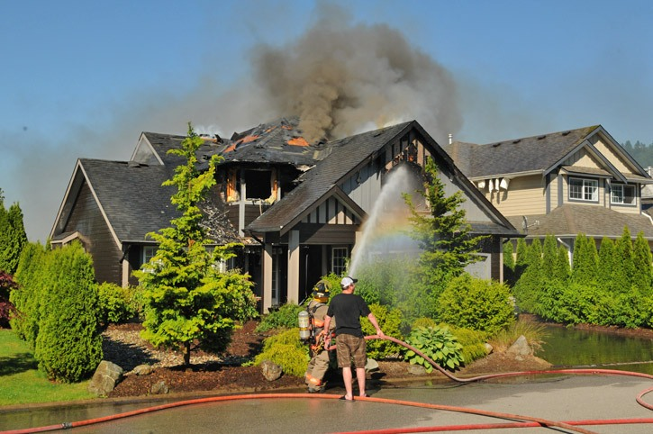 A man helps hold a fire hose as crews try to control a house fire on Daniel Drive in Promontory at about 5 p.m. Tuesday.