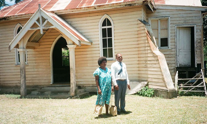 Pastor Thomas Niditause and his wife Mary outside the little Presbyterian church where he ministers in Lenakel