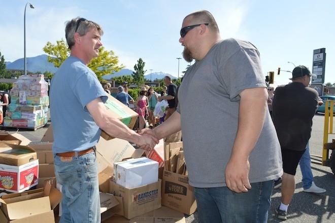 Chilliwack resident Jamie Cunningham shakes hands with truck driver and organizer Gordon VanLaerhoven