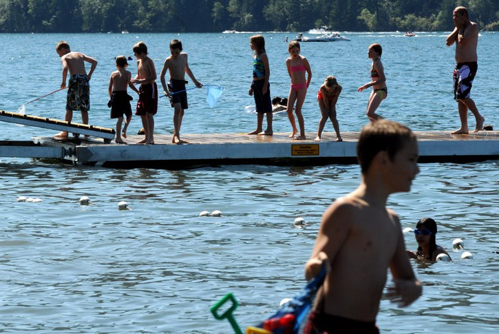 People take advantage of the hot summer weather at Entrance Bay in Cultus Lake on Saturday.