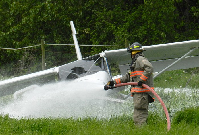 Firefights hose off the engine of a light plane that crashed in a field near Young Road on Fairfield Island in Chilliwack on Thursday. Two people were taken to hospital with minor injuries.