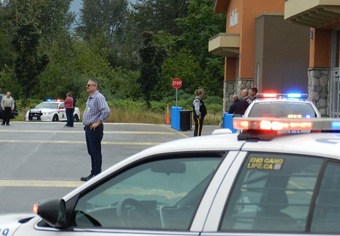 Staff and police keep people back from the Walmart in Chilliwack following an apparent bomb threat.