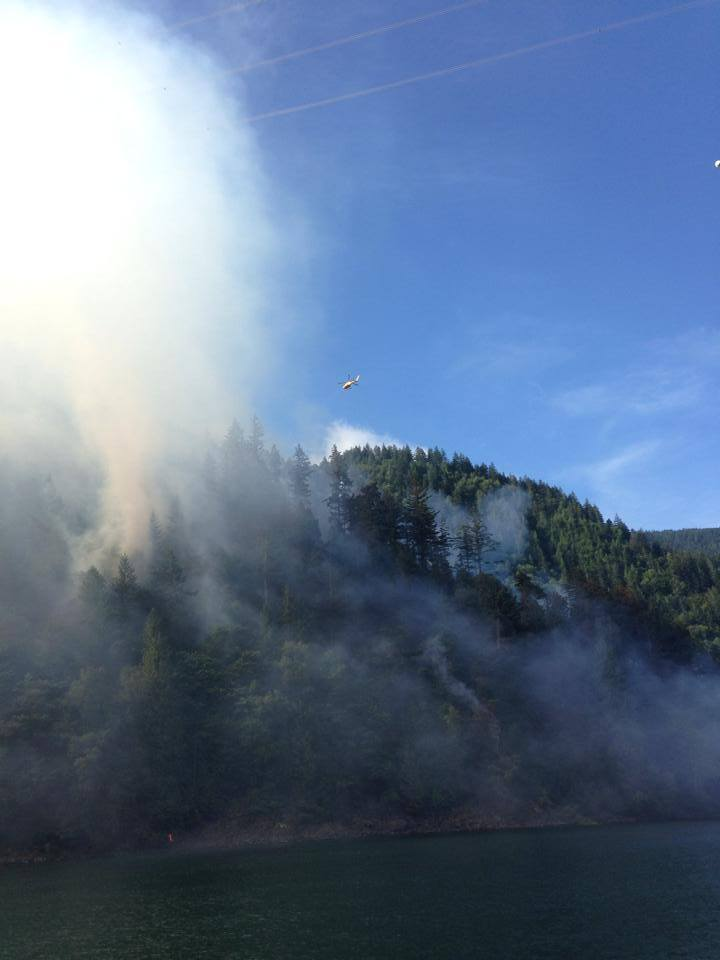 A helicopter flies over Agassiz Mountain