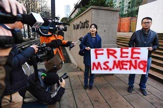 People hold a sign at a B.C. courthouse prior to the bail hearing for Meng Wanzhou, Huawei's chief financial officer on Monday, December 10, 2018. THE CANADIAN PRESS/Jonathan Hayward