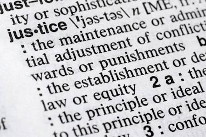 """In this Dec. 12, 2018, photo, """"justice"""" is displayed in a Merriam-Webster dictionary in New York. (AP Photo/Mark Lennihan)"""