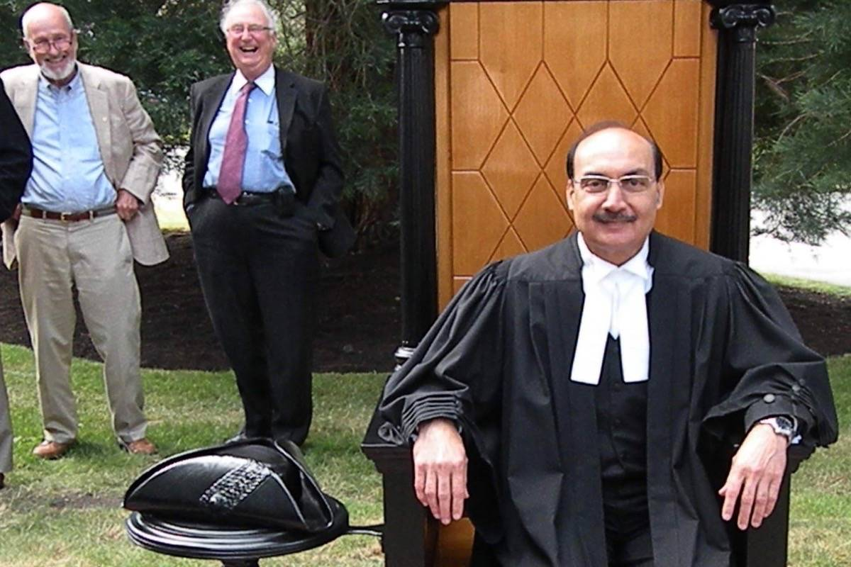 Former B.C. legislature clerk George McMinn (left) and others watch as Burnaby-Edmonds MLA Raj Chouhan, then assistant deputy speaker, tries out replica speaker's chair set up for tourists, spring 2013. (Tom Fletcher/Black Press)