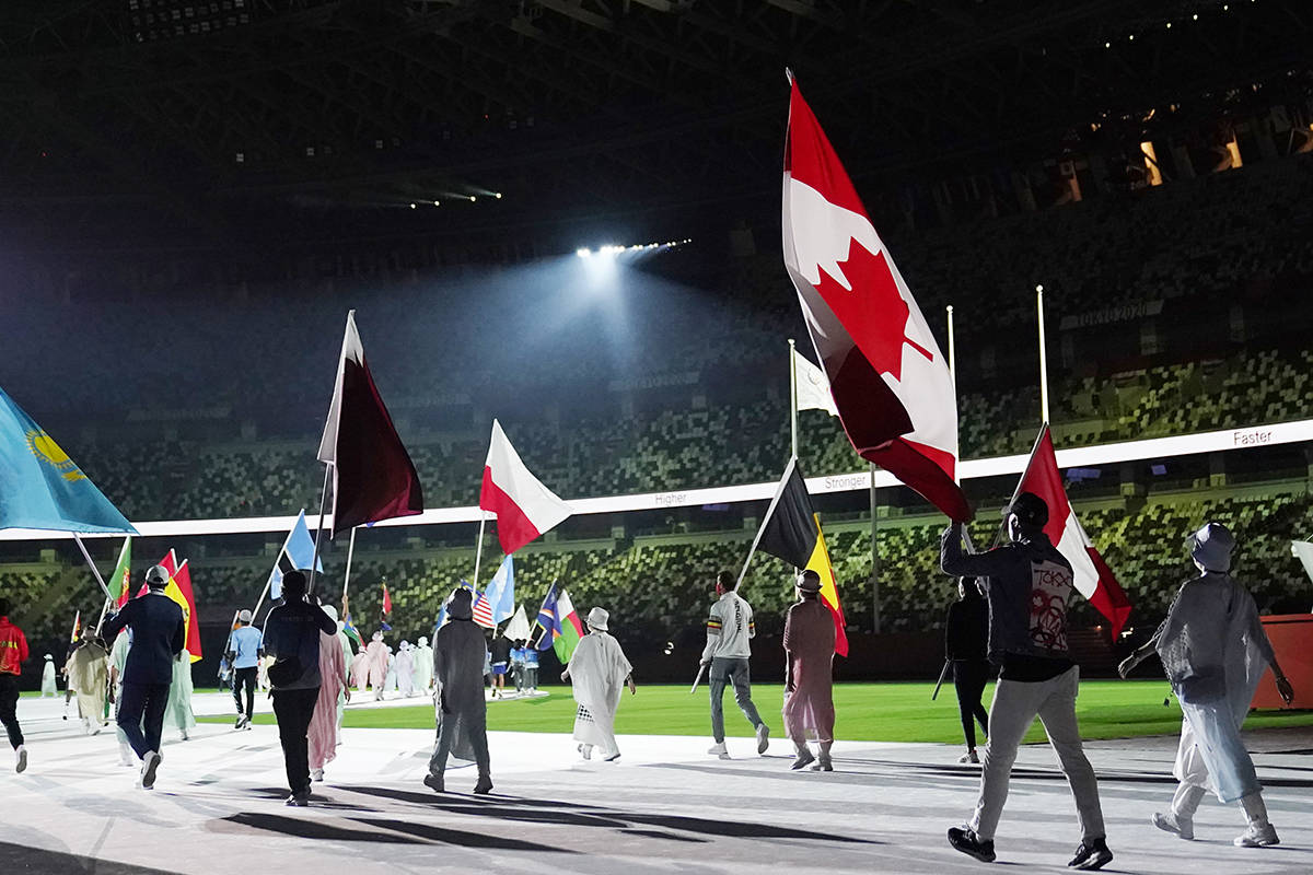 Damian Warner, of Canada, second from right, arrives during the closing ceremony in the Olympic Stadium at the 2020 Summer Olympics, Sunday, Aug. 8, 2021, in Tokyo, Japan. (AP Photo/David Goldman)