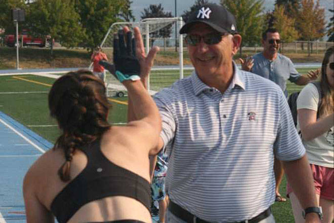Vernon resident Julie McCann (left) gets congratulations from her dad, Vernon native Ken Holland of the NHL's Edmonton Oilers, after setting an unofficial world record for being the fastest woman to cover 100 metres on all fours Monday, Aug. 9, at Greater Vernon Athletic Park. (Christine Castrucow photo)
