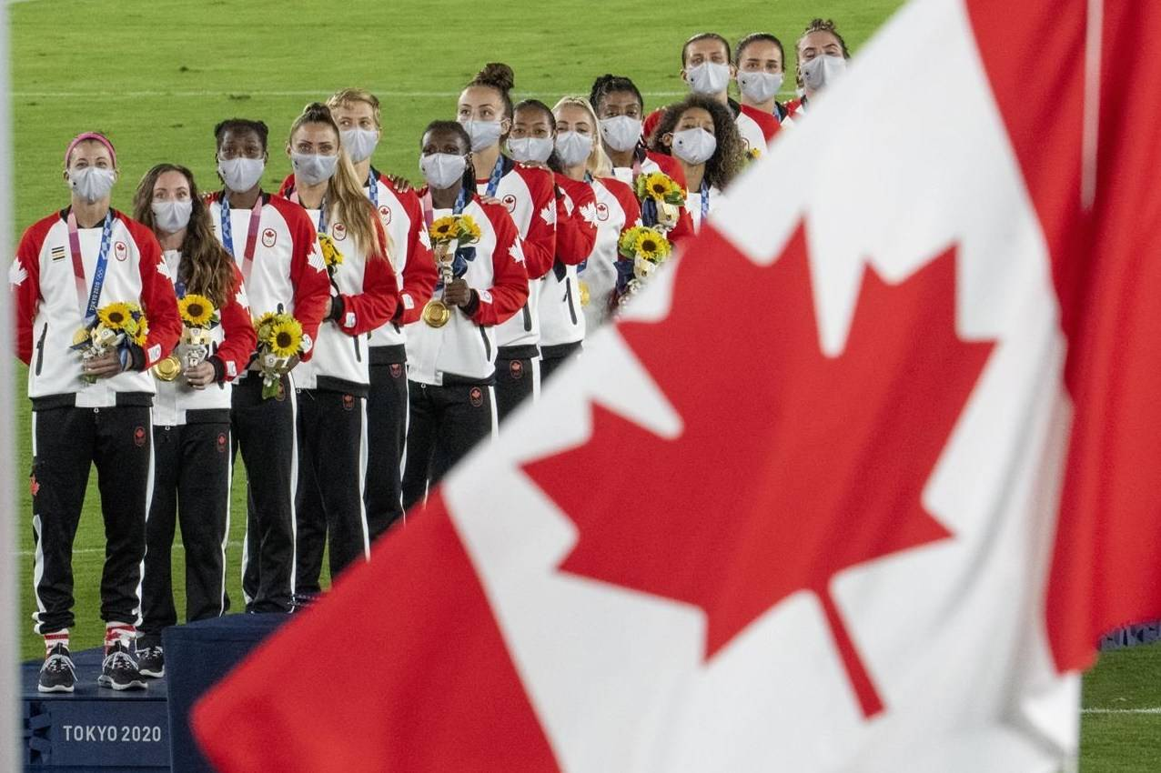 Members of the Canadian women's soccer team watch the flag rise after being presented with their gold medals at the Tokyo Olympics in Tokyo, Japan on Friday August 6, 2021.The CBC is touting record-breaking digital audiences for the 2020 Tokyo Olympics, while television viewership ranked it the most-watched network in Canada throughout the Games. THE CANADIAN PRESS/ Frank Gunn