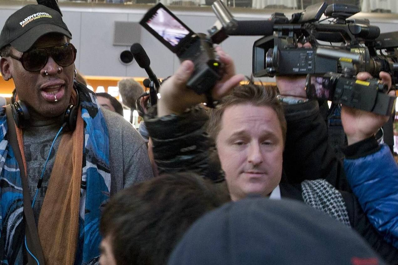 FILE - In this Dec. 19, 2013, file photo, Michael Spavor, center, an entrepreneur, is seen with former NBA star Dennis Rodman, left, on the arrival at the capital airport for a flight to North Korea, in Beijing, China. The Canadian entrepreneur who was charged with spying after his government arrested an executive of Chinese tech giant Huawei faces a possible verdict on Wednesday, Aug. 11, 2021 as Beijing steps up pressure on Canada ahead of a court ruling on whether to hand over the executive to face U.S. criminal charges. (AP Photo/Ng Han Guan, File)
