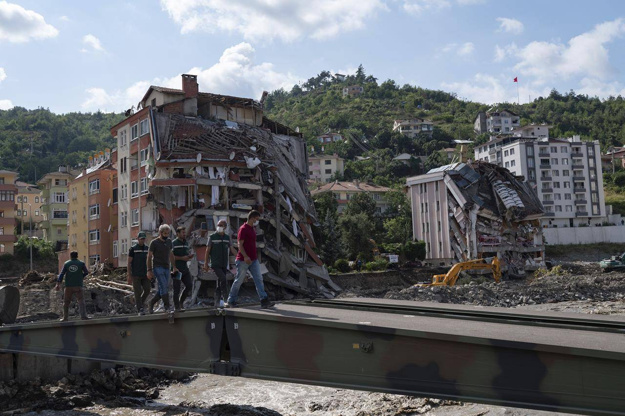 People walk on a temporary bridge set up by military in Bozkurt town of Kastamonu province, Turkey, Sunday, Aug. 15, 2021, after flooding. Turkey sent ships to help evacuate people and vehicles from a northern town on the Black Sea that was hard hit by flooding, as the death toll in the disaster rose Sunday to at least 62 and more people than that remained missing. (AP Photo)