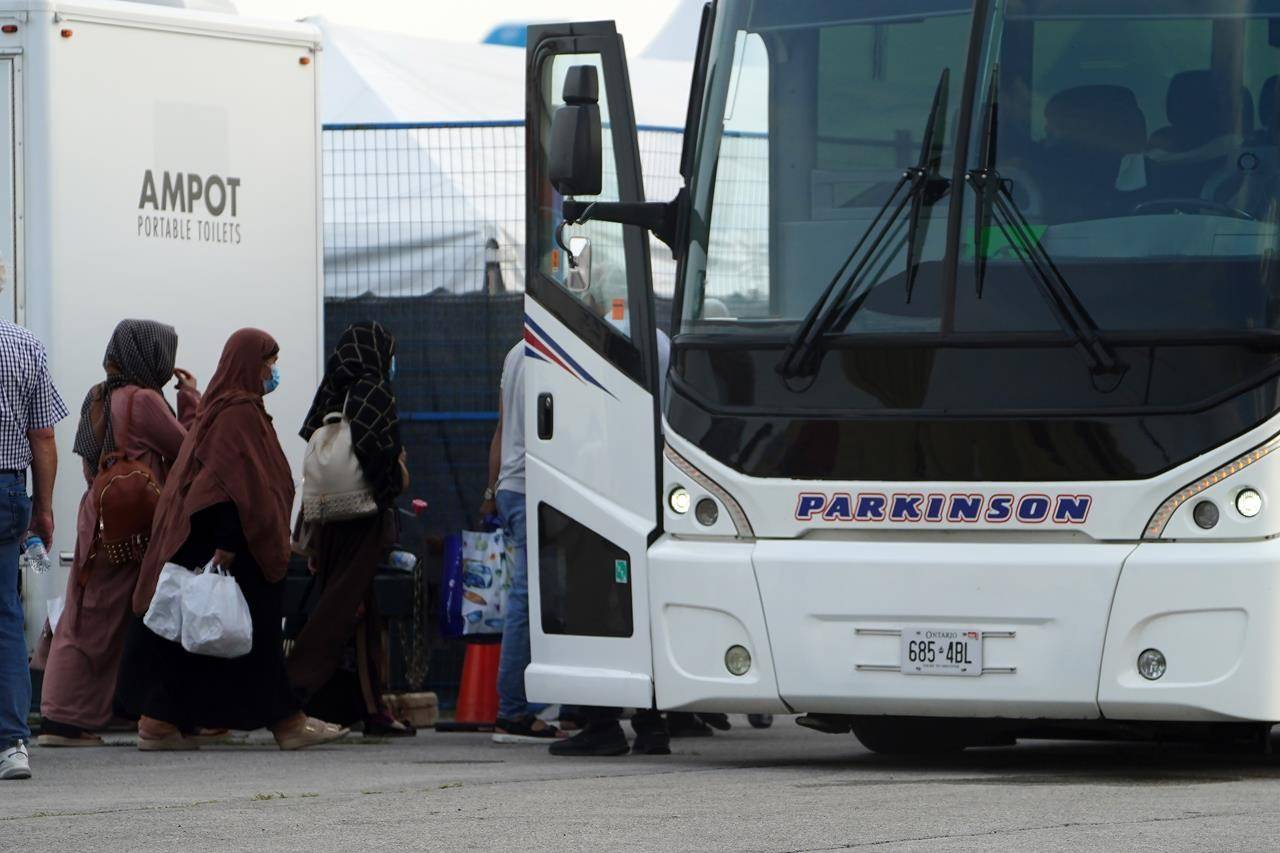Immigration Minister Marco Mendicino says his department will accelerate the processing of the families of interpreters and others who supported Canada's mission in Afghanistan to evacuate as many approved people as possible quickly. Refugees from Afghanistan and Canadian Citizens board a bus after being processed at Pearson Airport in Toronto, Tuesday, Aug 17, 2021, after arriving indirectly from Afghanistan. THE CANADIAN PRESS/Sean Kilpatrick