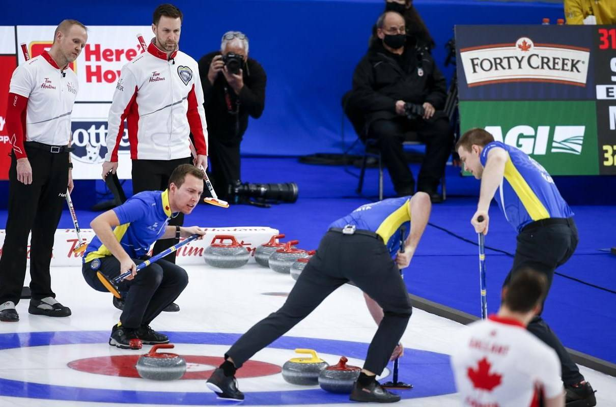 Team Alberta skip Brendan Bottcher, right, directs his teammates as Team Canada third Mark Nichols, left, and skip Brad Gushue look on at the Brier in Calgary, Alta., Saturday, March 13, 2021. Curling Canada says all athletes, fans, staff and media will have to be fully vaccinated against COVID-19 in order to participate in or attend affiliated events. THE CANADIAN PRESS/Jeff McIntosh