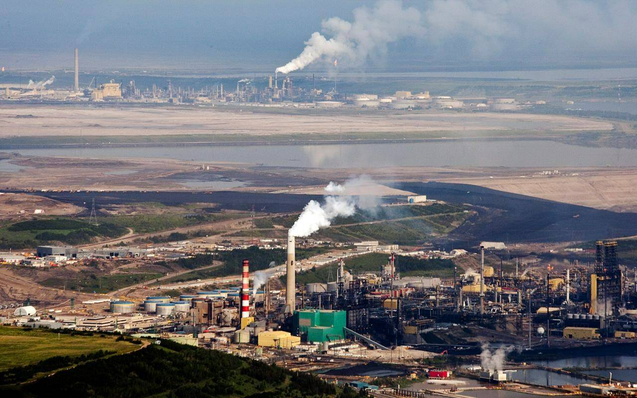 The Suncor oil sands facility seen from a helicopter near Fort McMurray, Alta., Tuesday, July 10, 2012. The insurance industry is grappling with whether to continue supporting fossil fuels in the face of the climate change threat. THE CANADIAN PRESS/Jeff McIntosh