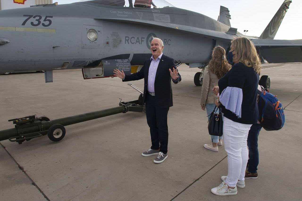 Conservative Leader Erin O'Toole, his wife, Rebecca, and their children check out a CF-18 Hornet parked near their campaign plane as they arrive in Edmonton, Saturday, Aug. 21, 2021. THE CANADIAN PRESS/Ryan Remiorz