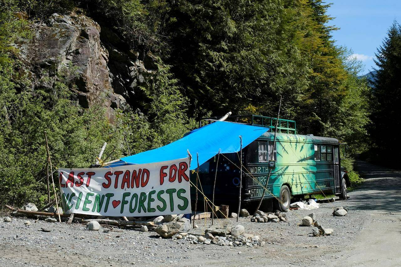 A bus and sign are shown near the Eden blockade in the Fairy Creek area near Port Renfrew, B.C., on May, 11, 2021. THE CANADIAN PRESS/Jen Osborne