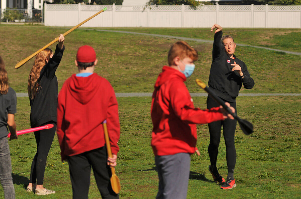 Olympic athlete Liz Gleadle shows Mt. Slesse middle school students how to throw a javelin during a visit to Chilliwack at Watson Glen Park on Friday, Oct. 1, 2021. (Jenna Hauck/ Chilliwack Progress)