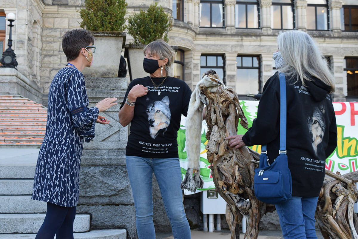 Wolf protection advocates Cheryl Alexander (centre) and Kelly Carson (right) present ministry staff member Katrine Conroy with a petition of over 500,000 signatures calling for the end to indiscriminate wolf hunting in B.C. (Kiernan Green/News Staff)