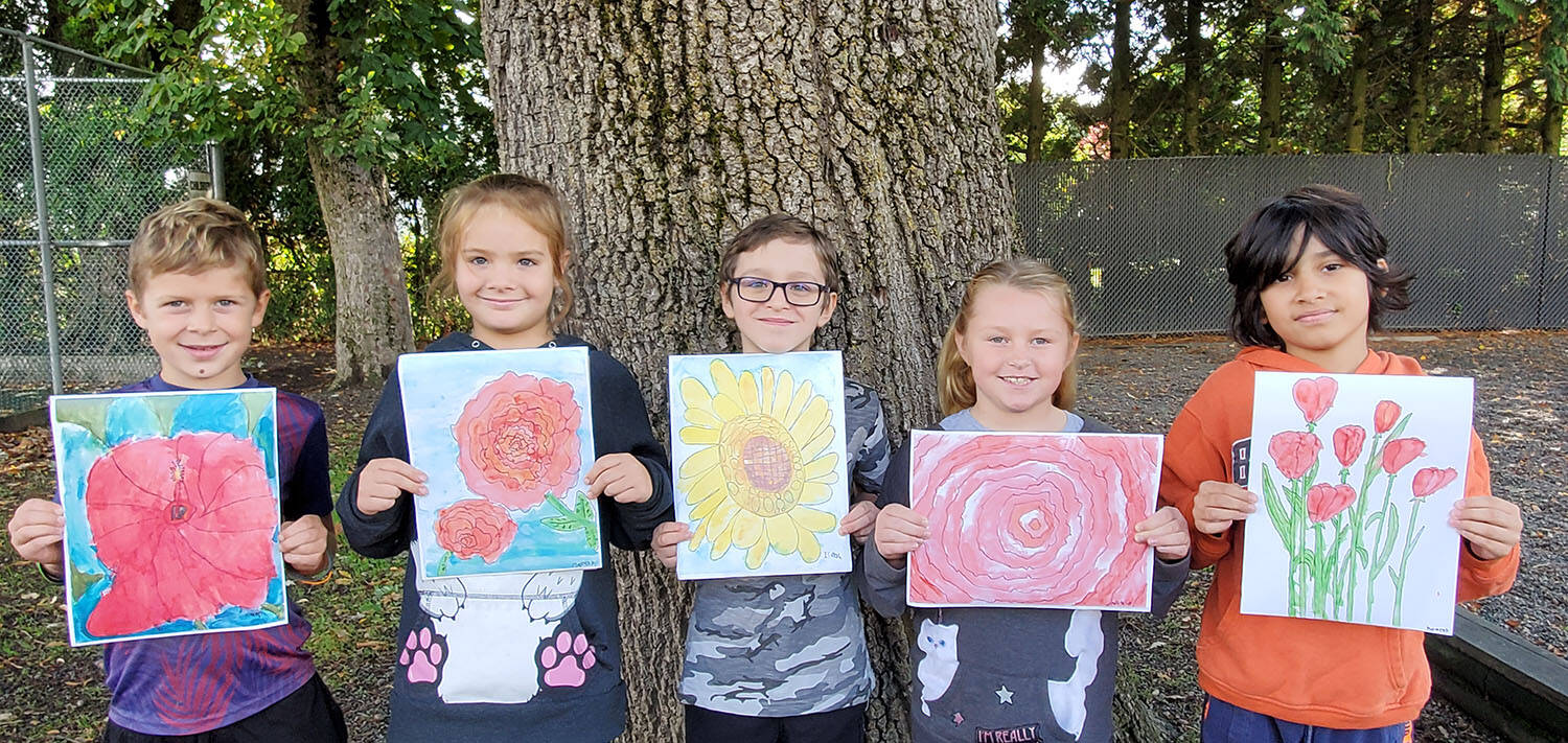 Some of the students in Debbie Mar's Grade 3 class at Upper Sumas Elementary display the watercolour paintings they created for seniors as part of the Planting Intergenerational Promises program. (Submitted photo)