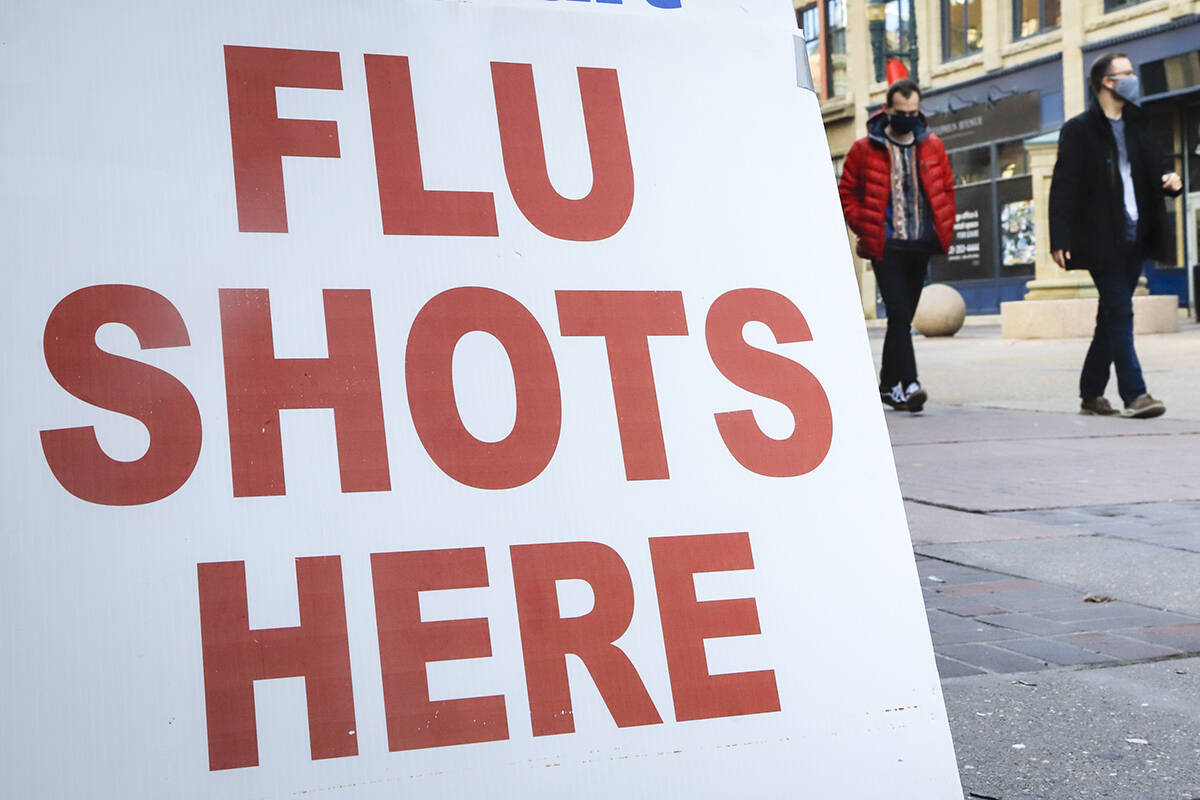 FILE – People wear masks as they pass a pharmacy offering flu shots in downtown Calgary, Alta., Friday, Oct. 30, 2020, amid a worldwide COVID-19 pandemic. THE CANADIAN PRESS/Jeff McIntosh